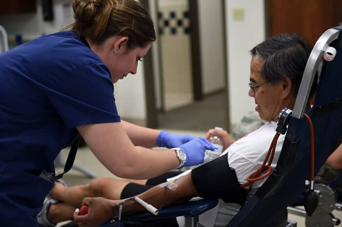 Phlebotomist drawing blood from a patient