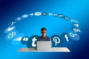 man working on laptop surrounded by social media icons