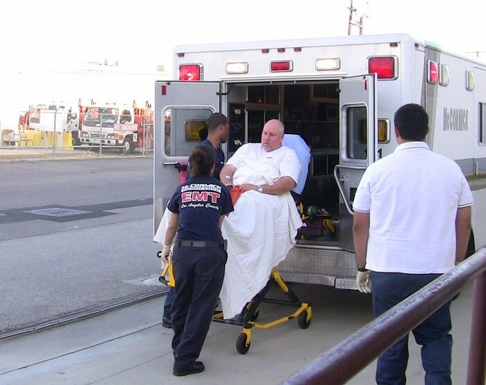 emergency medical technician putting patient in ambulance