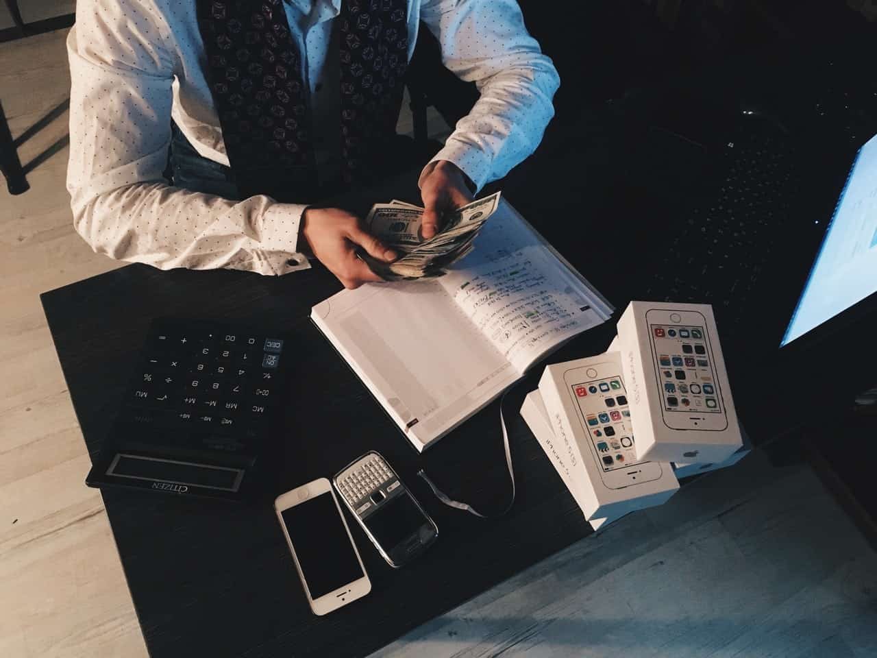 Man holding money, cellphone, calculator and laptop in the table with black background