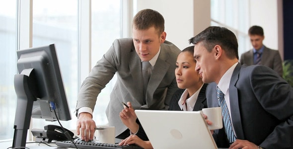 Group of business analysts looking at the monitor