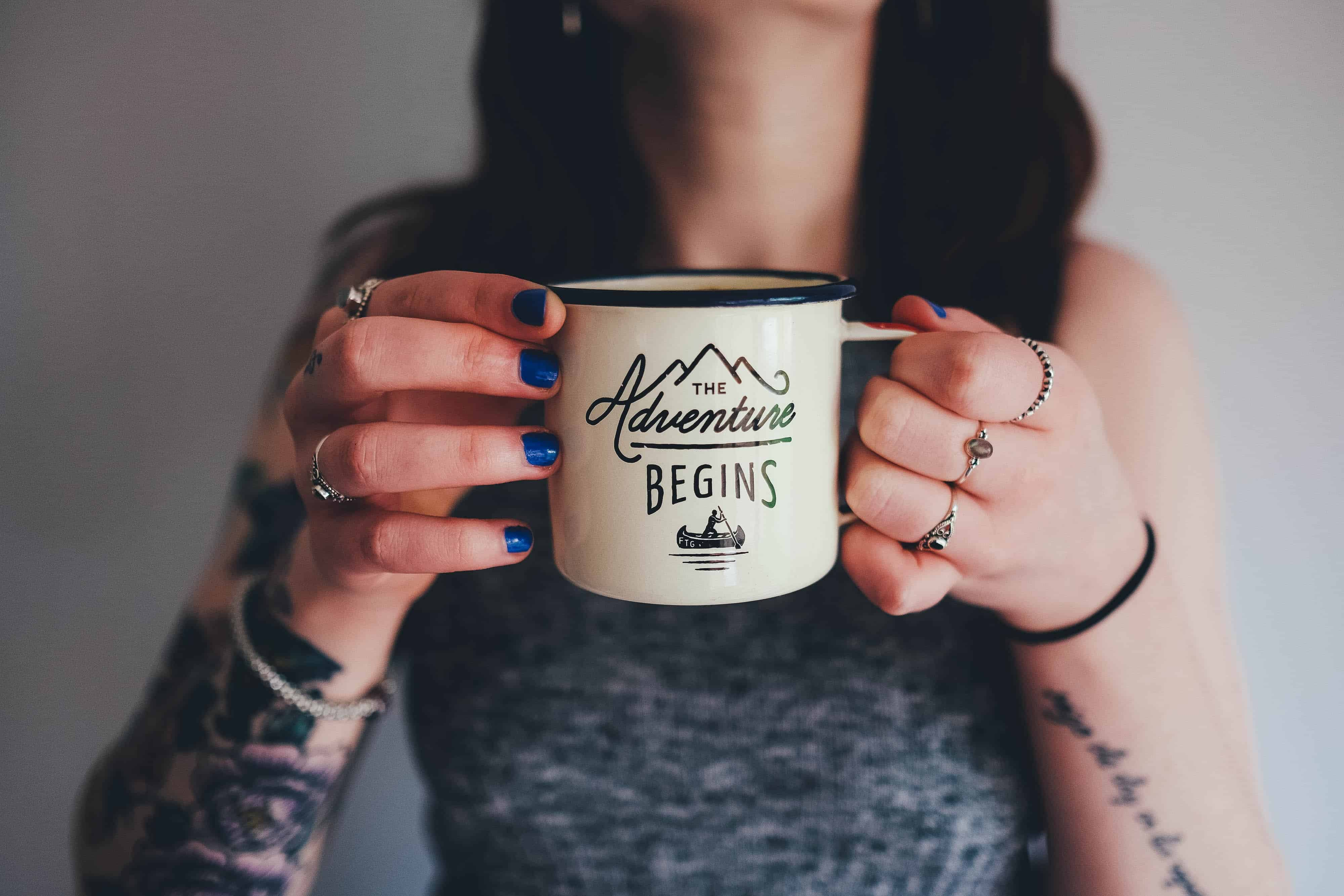 "professional woman with tattoos holding coffee cup that says ""the adventure begins"""