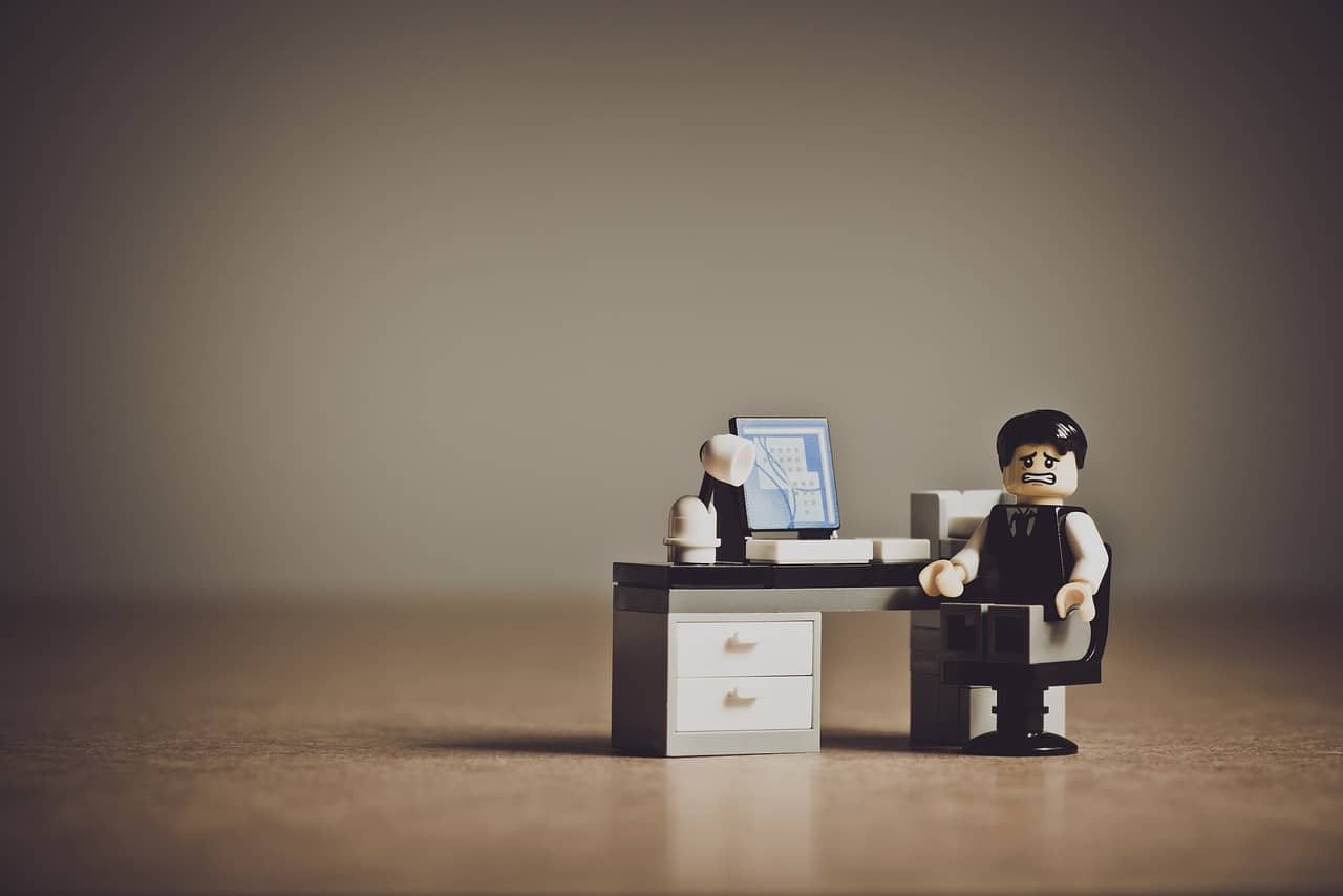 a lego employee looking scared as he sits on his chair with working desk