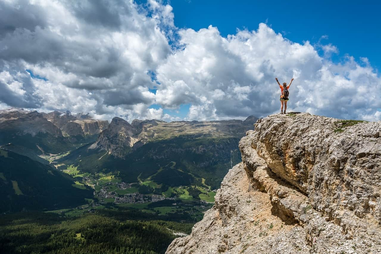 person with her arms raised in triumph as she stands on the top of a mountain ridge overlooking green valley